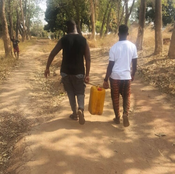 DOING HIS BIT: Tinie, right, takes water back to the village with his manager Dumi Oburota